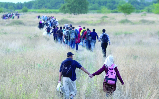 Migrants pass through the border from Greece into Macedonia. Photo by AFP